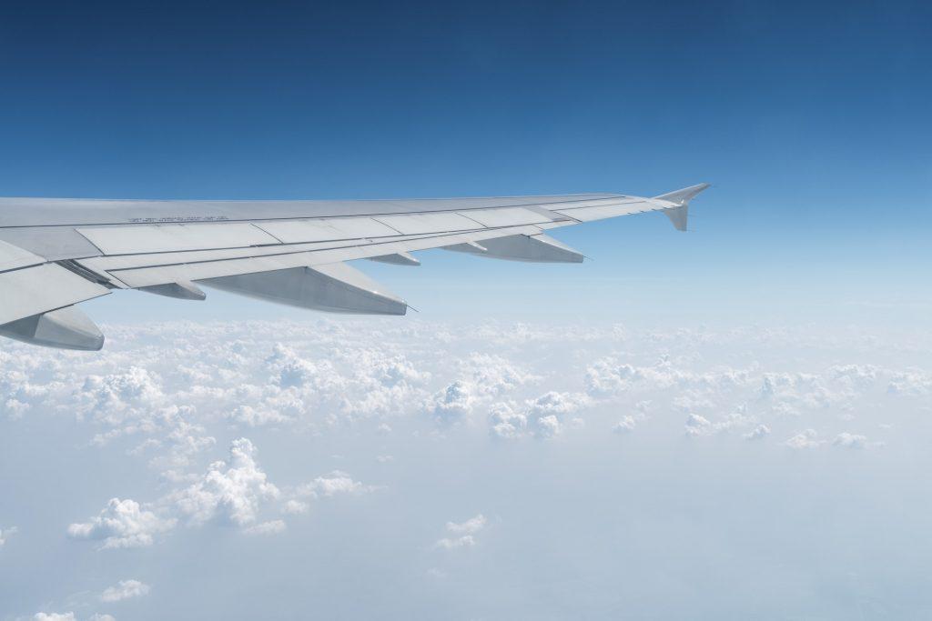Flygplansvinge i himlen med moln nedanför