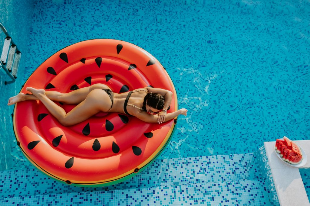 Kvinna på rund luftmadrass i swimmingpool